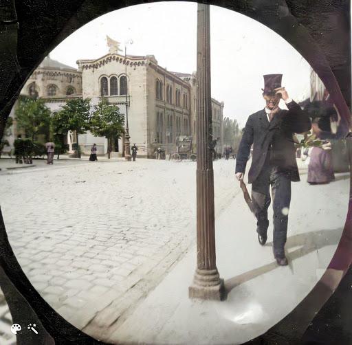 En mand tipper på hatten, mens han passerer en lygtepæl på fortovet af en brostensbelagt gade. På tværs af vejen er der nogle træer, en elegant bygning og andre mennesker, der spadserer omkring
