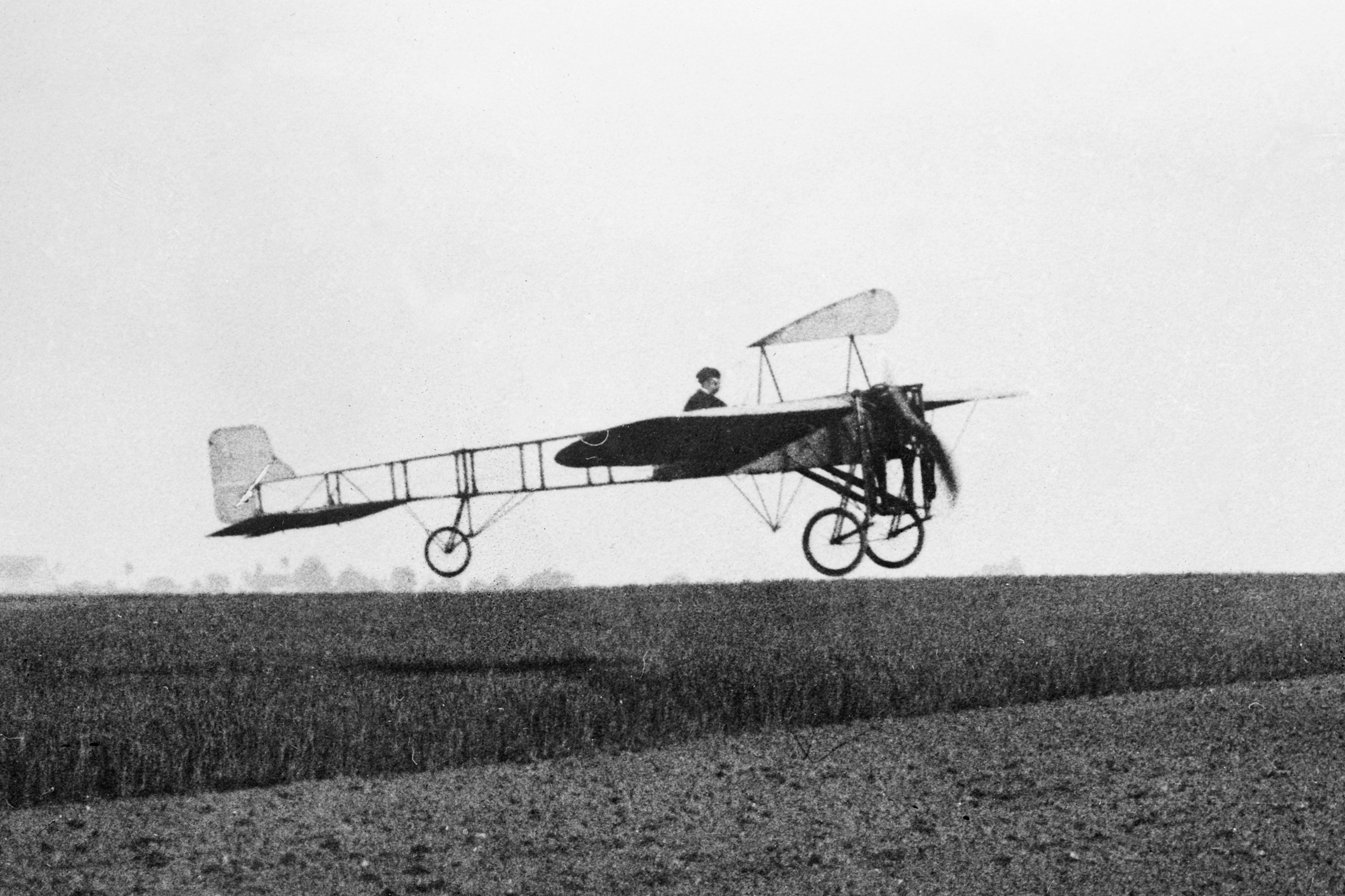 Louis Blériot in flight over field, 1909.